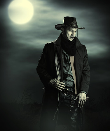 Handsome man in cowboy costume stay in steppe at night with full moon. Vampire Hunter Stock Photo