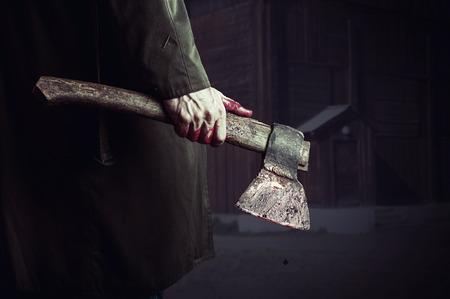 Axe met bloed in mannelijke hand. moordenaar of slager, halloween thema
