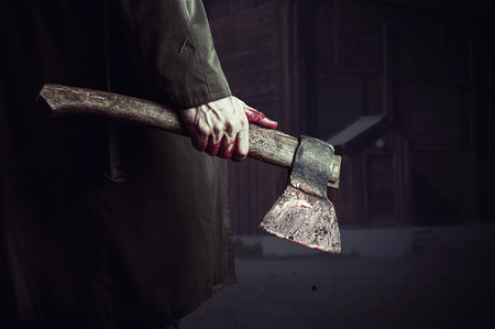 Axe with blood in male hand.  murderer or butcher, halloween theme