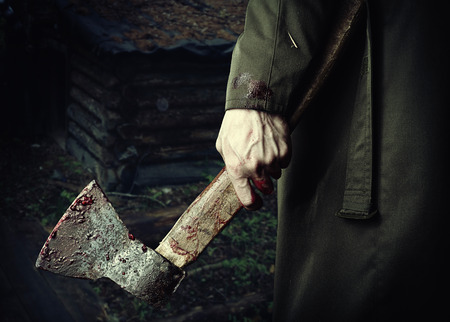 murderer: Axe with blood in male hand.  murderer or butcher, halloween theme