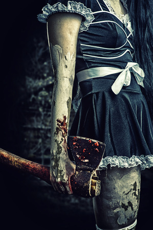 Horror. Dirty womans hand holding a bloody ax outdoor in night forest photo