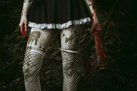 Halloween horror. Dirty womans hand holding a bloody ax outdoor in forest