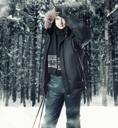 Young man skier wearing black fur hood winter jacket and holding sticks in winter forest photo