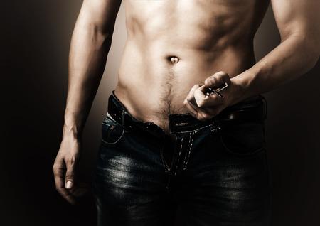Hombre mostrando su musculoso cuerpo. Stripper desabrocha los pantalones vaqueros y cinturón