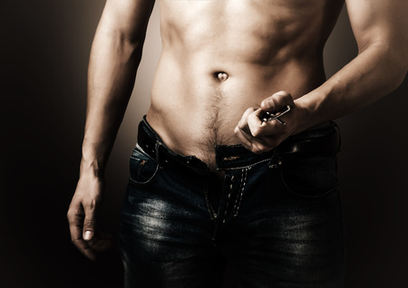 Man showing his muscular body. Stripper unzips jeans and belt Stock Photo