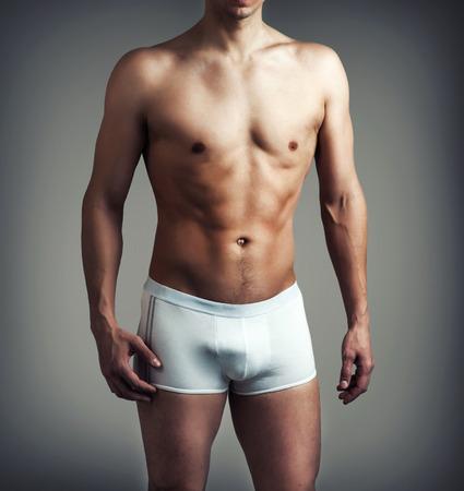 灰色の背景に白の下着でポーズをとって筋肉の若いセクシーなハンサムな男 写真素材
