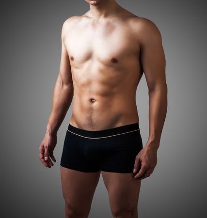 Muscular young sexy handsome man posing in black pants on gray background. underwear model