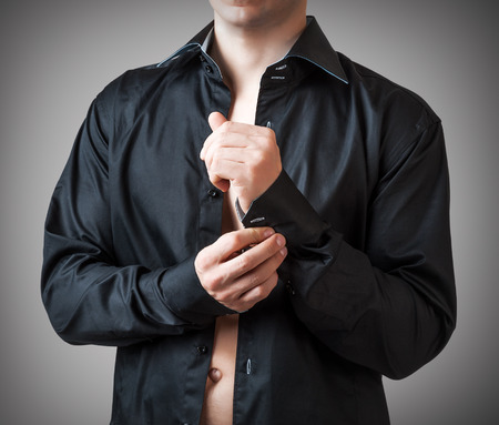 enticement: Man Buttons sleeve black shirt on gray background. Studio shot Stock Photo