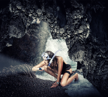 Adventure. Woman traveler and explorer in sea cave, shining a flashlight into the darkness searching treasures