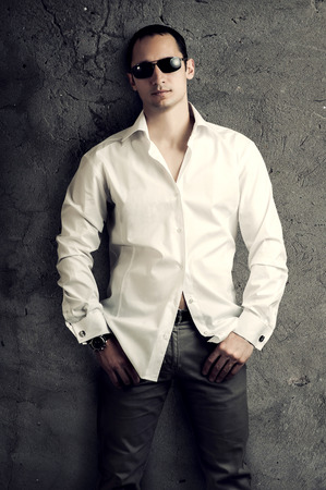 Fashion portrait of young sexy man wearing white luxury shirt and sunglasses poses about gray wall photo
