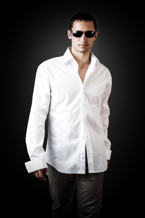 Fashion portrait of young sexy man wearing white luxury shirt and sunglasses walking on black background