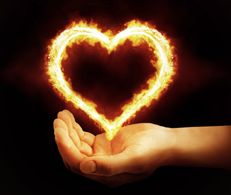 fire shield: Hand holding fire heart on black background. Saint valentines day or hot love concept Stock Photo