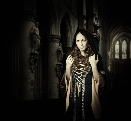 vestido medieval: Mujer hermosa con un vestido medieval vendimia con la capilla de la iglesia gótica
