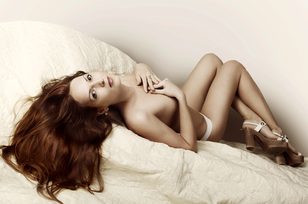 Beautiful slim woman with perfect body and long hair wearing white pants and lying on bed photo