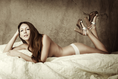 hot pants: Beautiful slim woman with perfect body and long hair wearing white pants and lying on bed