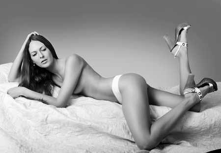 wearing sandals: Black and white style. Beautiful slim woman with perfect body and long legs wearing white pants and lying on bed Stock Photo