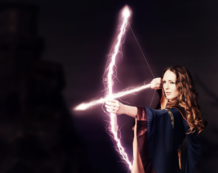 dark elf: Beautiful fairy woman archer with a magic bow at night on dark background Stock Photo