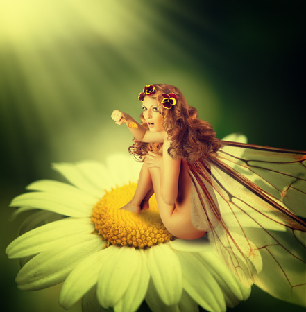 redhaired: Little beautiful fairy woman with wings is sitting on a chamomile flower and eating pollen Stock Photo