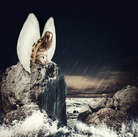 water wings: Sad woman fallen angel with white wings sitting on a rock in the sea