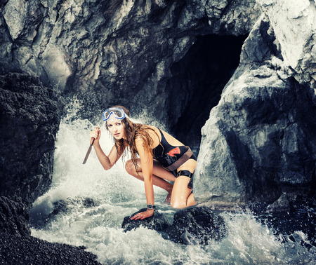 careful: Adventure. Careful woman with a knife looks out from a sea cave
