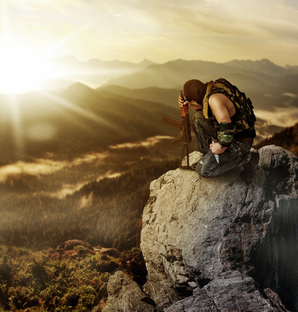Military man warrior praying before the fight and sitting on a rock on summer morning