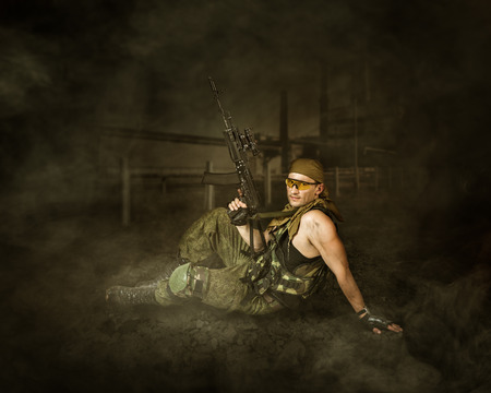 automatic machine: Military man soldier Holding automatic machine gun and sitting on a ground Stock Photo