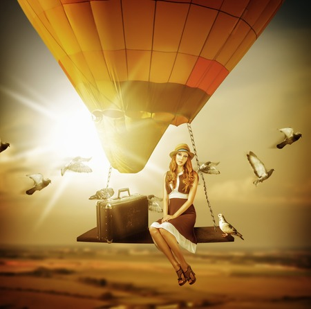 flying woman: Fantasy travel. Young woman flying a balloon