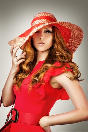 red hat: Fashion portrait of woman wearing vogue red hat and dress isolated on gray background Stock Photo