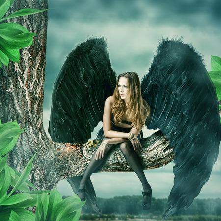 Mooie vrouwelijke zwarte engel zittend op een boom Stockfoto