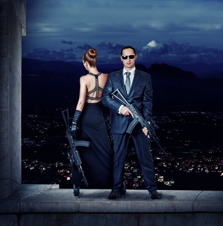 secret agent: Fashionable couple  woman and man holding automatics