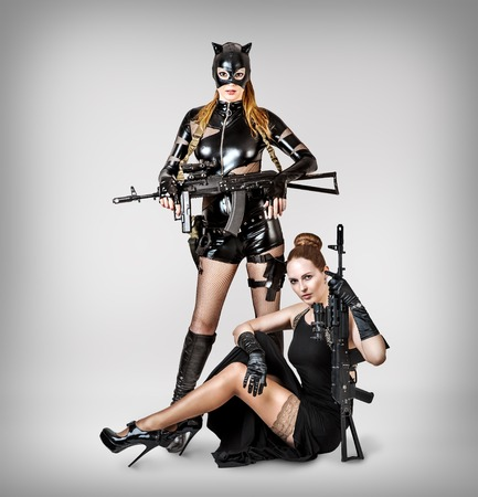 Two sexy models holding automatics on gray background in studio
