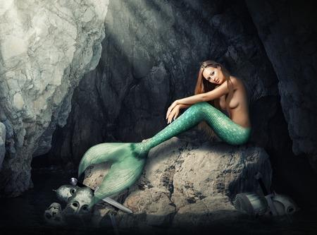 Mooie vrouw zeemeermin zittend op stenen in een donkere grot. Helmen en schedel gebroken zwaarden in water Stockfoto