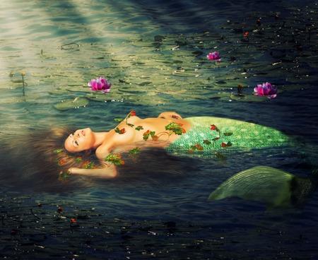 tail woman: Mujer sirena hermosa con una cola de pez descansando en el agua del estanque de lirios Foto de archivo