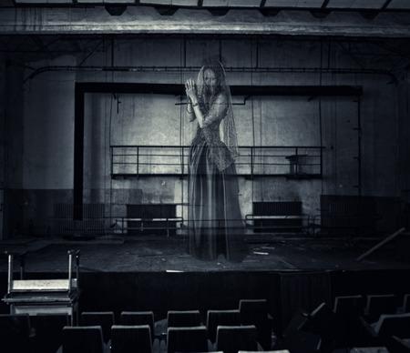 halloween horror. borroneada fantasma de la mujer la actriz en el escenario del antiguo teatro fue destruido Foto de archivo