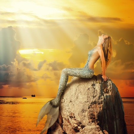 surreal: Fantasy. beautiful woman mermaid with fish tail and long developing hair swimming in the sea underwater Stock Photo