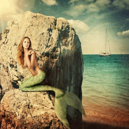 Sexy sirena hermosa mujer con cola larga sentada en una roca sobre el mar. Escondiéndose de veleros Foto de archivo