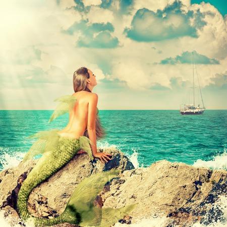 Schöne Meerjungfrau mit Fischschwanz, die auf Felsen und schaut auf einem Schiff auf dem Horizont