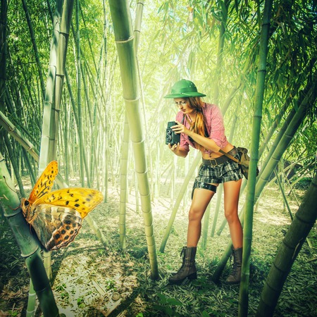 tropics: Young retro styled woman traveler in tropics holding vintage camera  photographed Big tropical butterfly