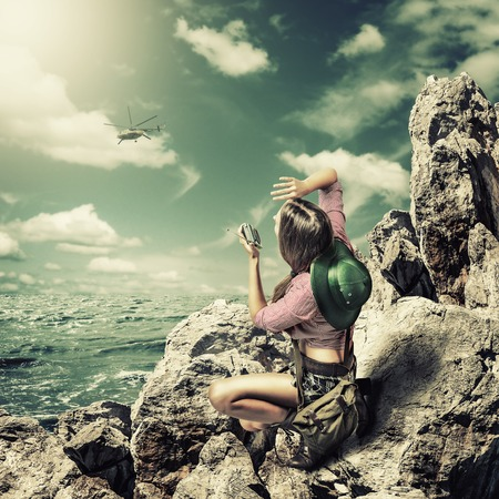 short wave: Young woman traveler sitting on a rock about sea. Says on the old Portable radio transmitter with the helicopter Stock Photo