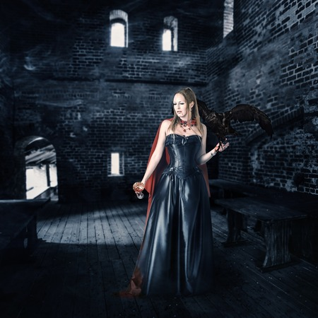 young beautiful female vampire aristocrat with a cup of blood stands in the old castle photo