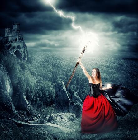 vestido medieval: bruja hacer magia y controla el clima. dispara un rayo en el cielo de las varas mágicas