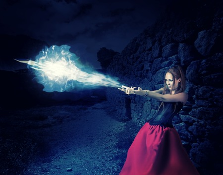 beautiful woman witch trains in medieval castle cast magic  blue cold ball of ice from hands photo