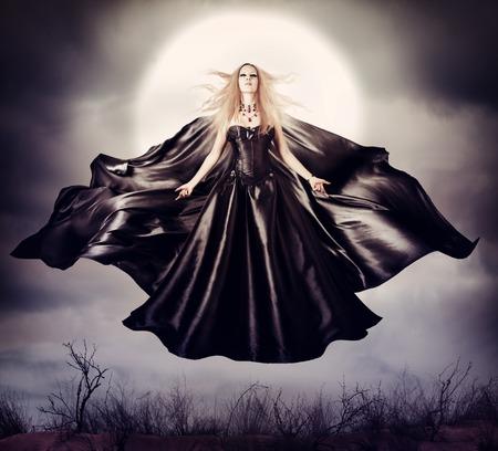 mago: Hermosa mujer volar bruja de halloween en el exterior de la medianoche sobre la luna llena con negro manto desarrollo Foto de archivo