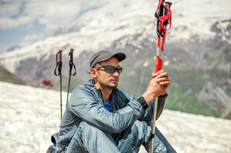 alpinist: Young man mountaineer sitting on a snow hillside near top of mount Cheget and holding trekking pole. Mountain Elbrus on background
