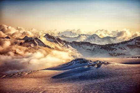 montañas nevadas: Hermoso paisaje - cresta de la montaña del Cáucaso occidental en nubes al atardecer o al amanecer