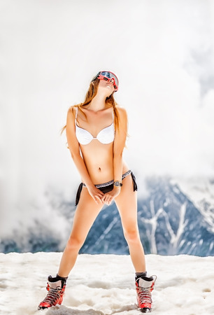 bikini top: Beautiful slim and fit woman wearing bikini and Plastic mountain boots stay on snow on the slopes of high mountains