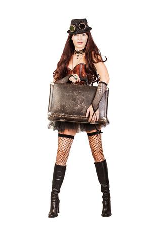 stay beautiful: Retrato de una hermosa mujer que viaja steampunk permanecer toda su altura y la celebraci�n de la maleta retro aislado en el fondo blanco Foto de archivo