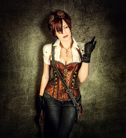 steampunk: Portrait of a beautiful steampunk woman wearing vintage corset and retro goggles on old grange background
