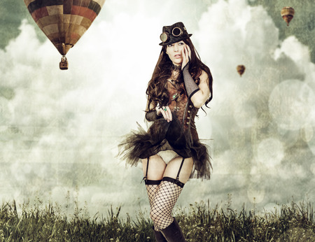 steampunk goggles: worn card in sepia retro style. Beautiful young steampunk woman wearing old-fashioned fantasy clothes outdoor. Balloons flying in sky in background Stock Photo