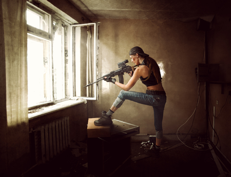 post apocalypse: Young beautiful woman sniper and Soldier aiming a rifle at the window. She is in old room of abandoned building